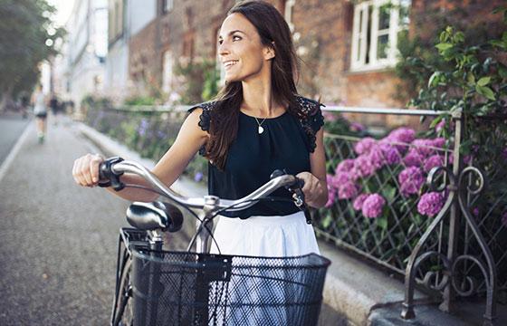 Sonriente mujer con bicicleta caminando por la calle-Jacob Ammentorp Lund-Istock