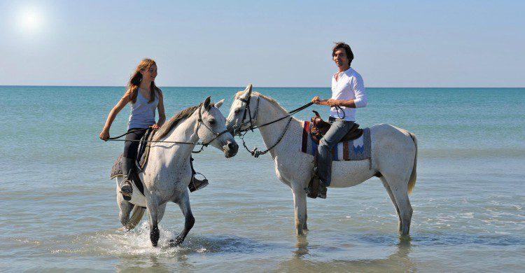 Hombre y mujer a caballo por la playa de Sayulita, Nayarit