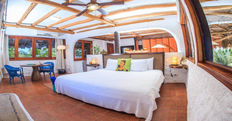 Habitación de lujo del hotel Las Nubes de Holbox con sabanas blancas y almohada de Frida Khalo