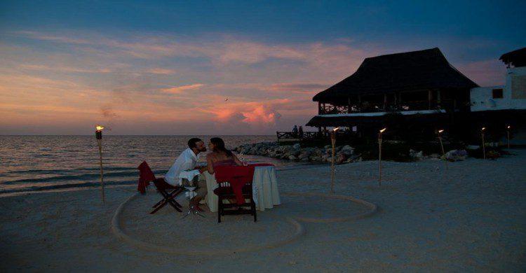 pareja cenando a la orilla del mar con corazón dibujado en la arena