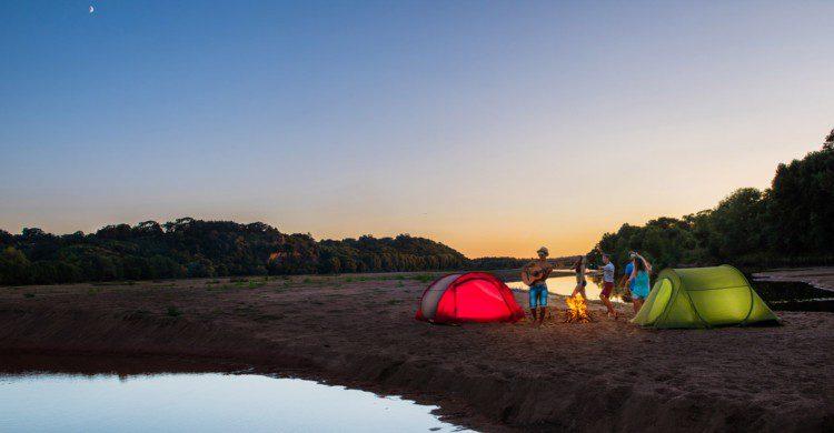Jóvenes acampando a la orilla del mar al anochecer