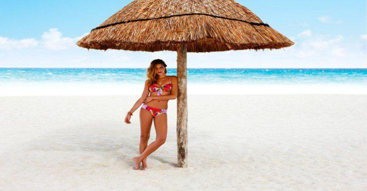 Mujer joven en traje de baño en la playa bajo una palma