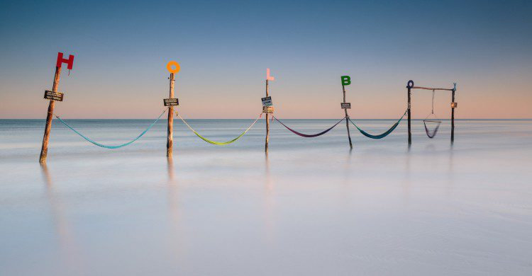 Letrero de Holbox a la orilla del mar cristalino
