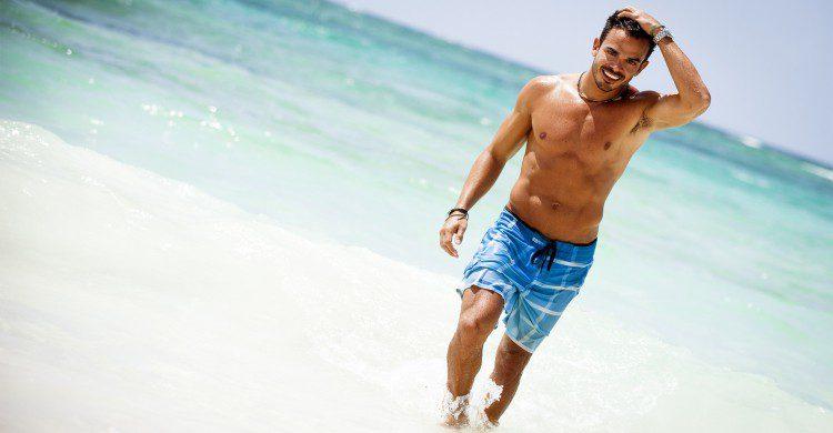Hombre musculoso caminando a la orilla del mar turquesa de día
