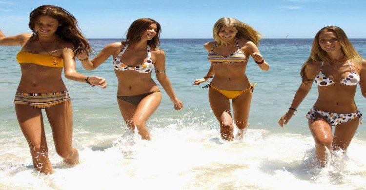 Cuatro mujeres en traje de baño saltando a la orilla del mar