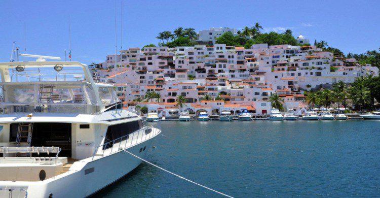 Playa de Manzanillo Colima de día con barco blanco en el mar azul