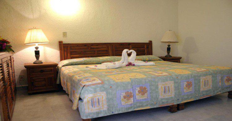Habitación con lampara en cendida y cama matrimonial en el Hotel Suites Jazmin