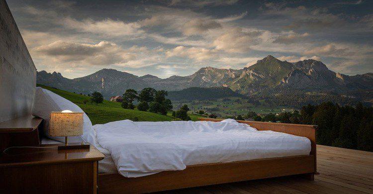 Cama con sabanas blancas, buros con lamparas encendidas al aire libre con vista a las montañas