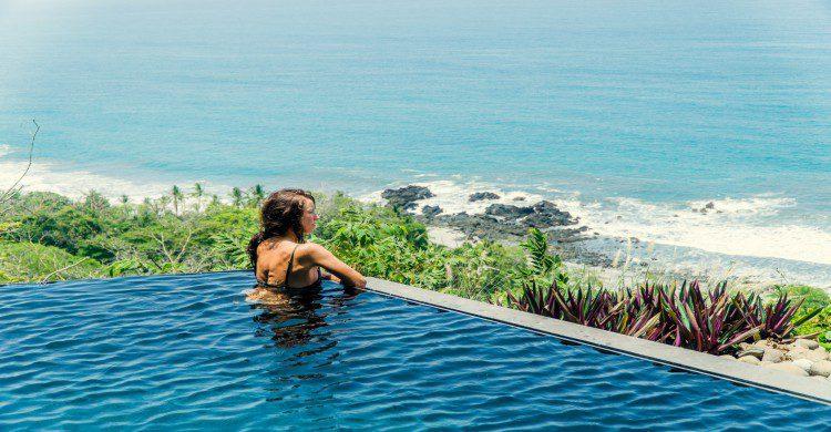 Mujer en una piscina viendo al mar en Montezuma, Costa Rica