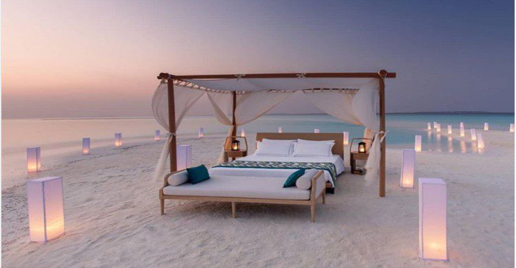 Cama lujosa con velas asobre la arena blanca a la orilla del mar al atardecer