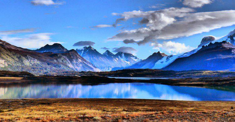 Montañas cubiertas de nieve, cielo azul y lago en Patagonia, Argentina