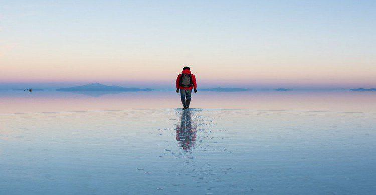 Hombre con mochila caminando en medio de El Salar, Bolivia