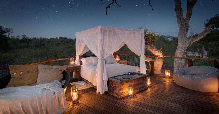 Cama lujosa con lamparas al rededor al aire libre de noche con estrellas en el cielo