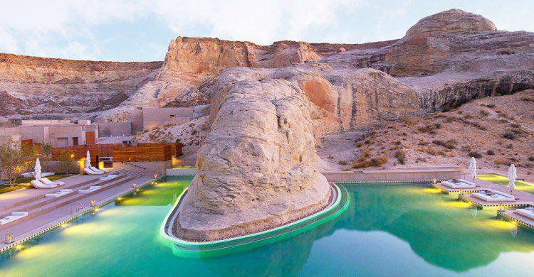 Piscina turquesa en medio del desierto con camas al rededor al aire libre