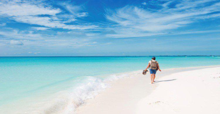 Persona caminando en playa caribeña de Santiago, Cuba con arena blanca y mar turquesa