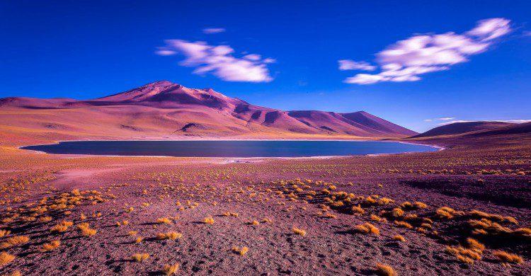 Cielo azul, lago y montañas en tonos rojizos purpura en el Desierto de Atacama, Chile