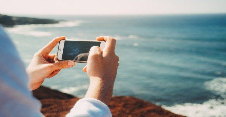 Hombre tomando una foto del mar con celular de día