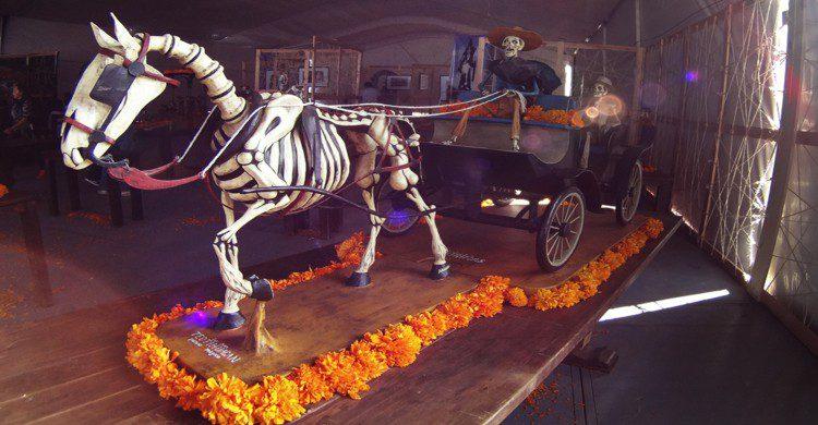 Escultura de hombre conduciendo una carreta con caballo calavera