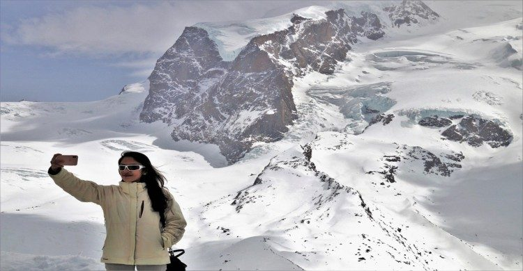 Mujer en las montañas nevadas tomandose selfie con lentes oscuros