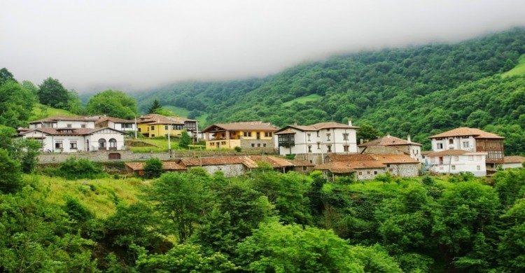 Ciudad de Ponga, en Asturias de día con neblina y vegetación verde
