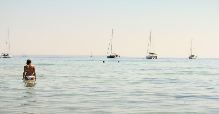 Mujer con trajhe de baño blanco en mar de Ibiza de día con barcos de fondo
