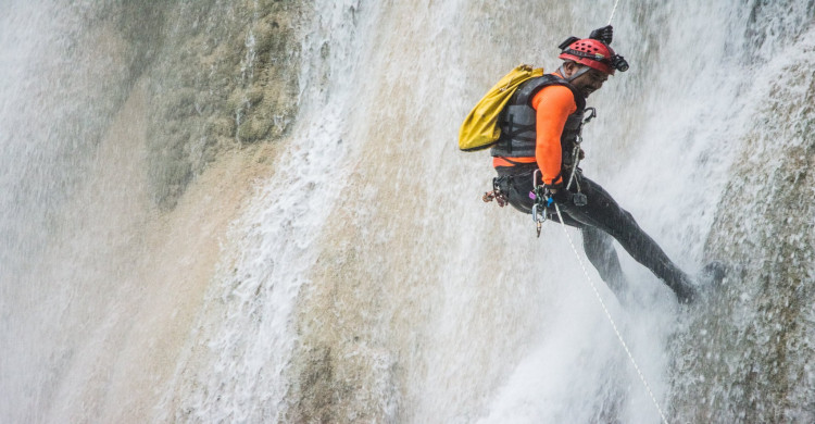 Hombre practicando rappel en cascadas Las 3 Tzimoleras con equipo de protección