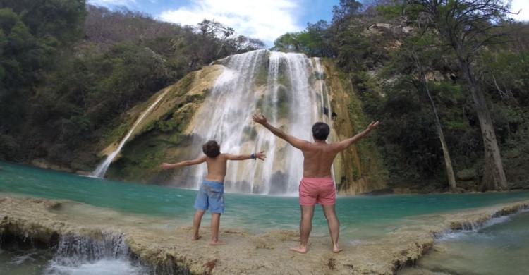 Hombre y niño de espaldas viendo cascada de día