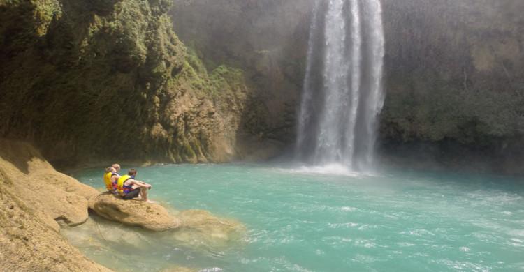 Dos jóvenes al pie de cascada con pozas turquesas de día