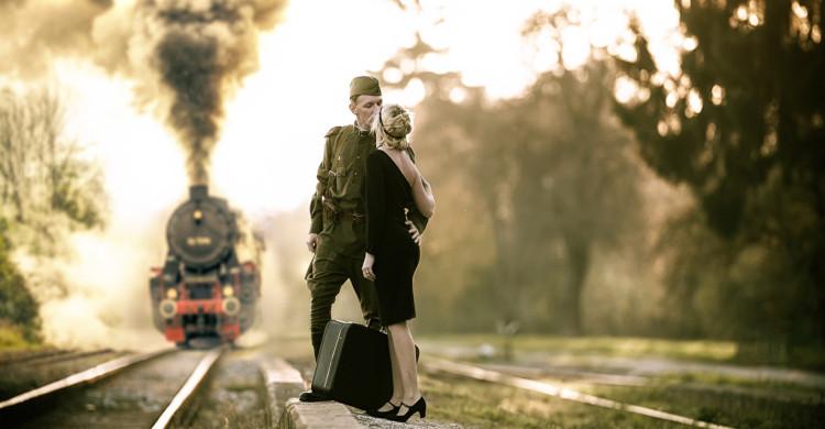 pareja besándose en las vías del tren de día