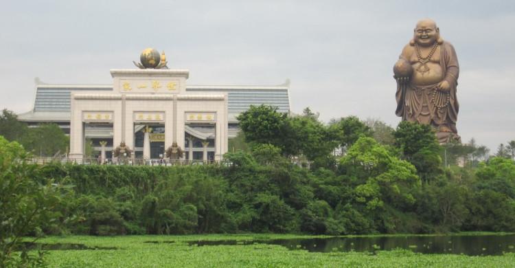 Estatua de Gran Buda sosteniendo a la Tierra al lado de edificio