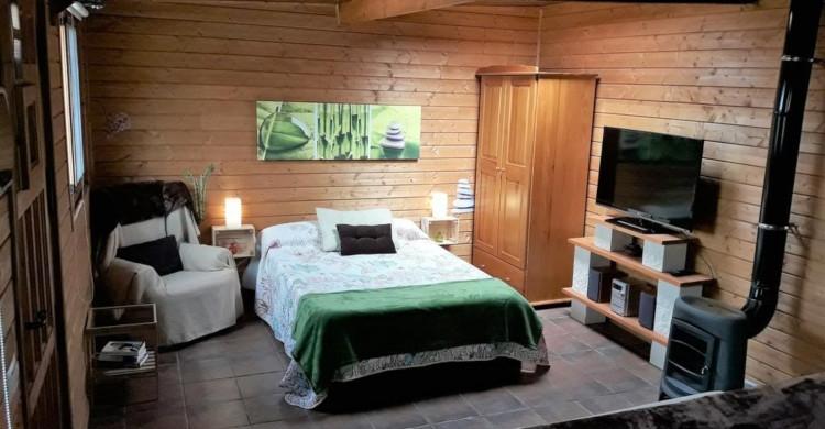 Recamara al interior de una cabaña de madera con televisión