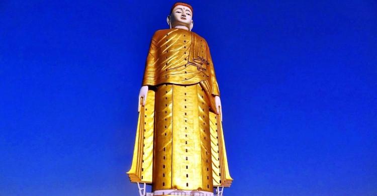 Estatua de Buda dorada con cielo azul de fondo