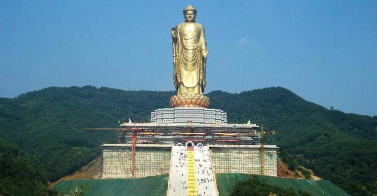 Estatua dorada con cielo azul y montañas de día
