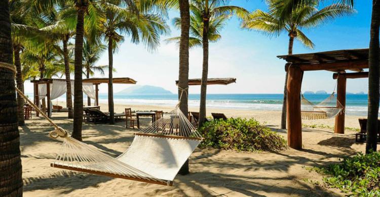 arena blanca con palmeras y hamaca en Ixtapa Zihuatanejo de día