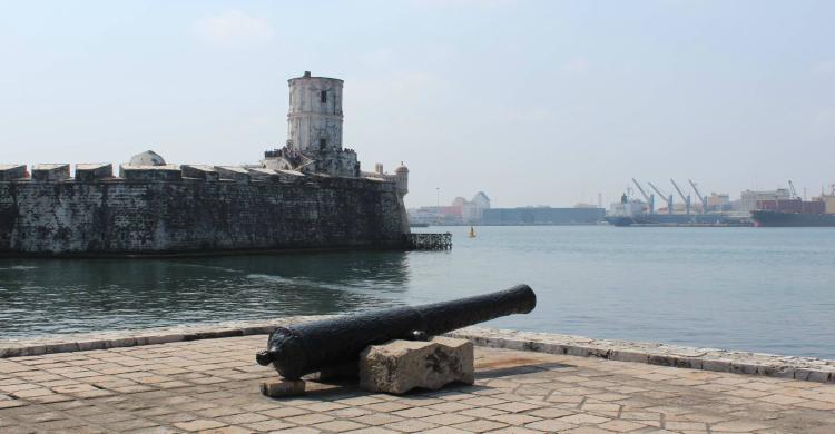 Cañón con fuerte de San Juan de Ulúa de fondo de día con mar azul