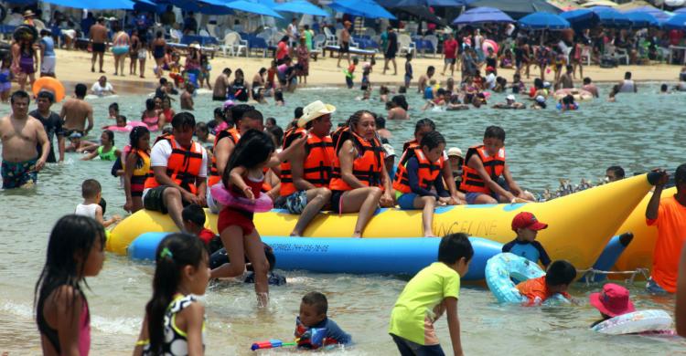 Turistas en la banana en playa de Acapulco de día