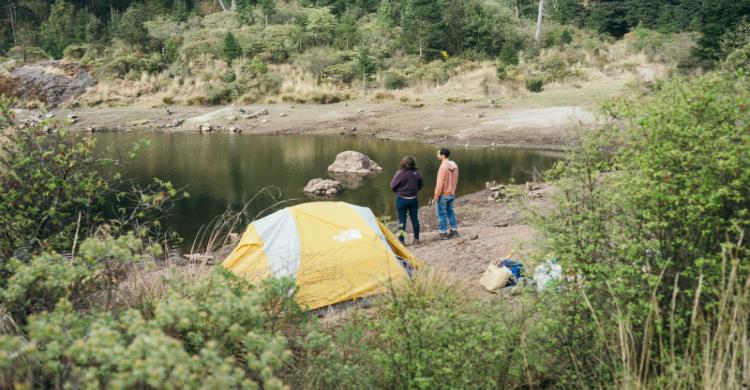 pareja a la orilla del lao con tienda de acampar de día en el bosque