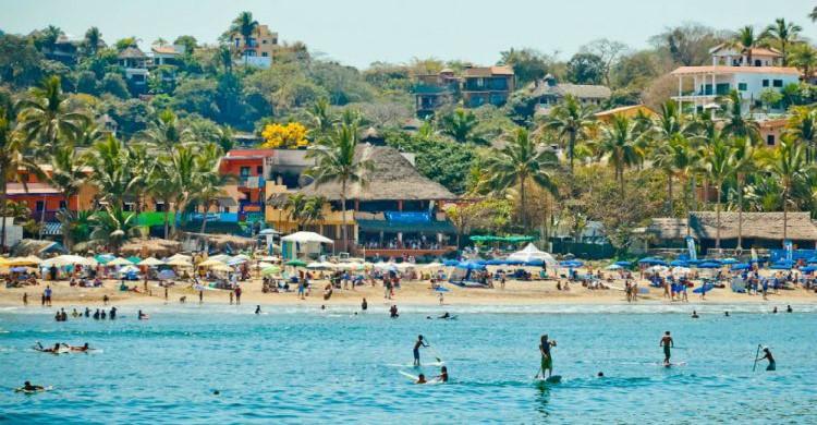 Playa de Sayulita de día con mar azul y turistas